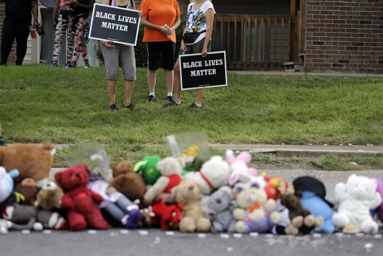 People wait to take part during a parade in honor of Michael Brown near a memorial to Brown Saturday, Aug. 8, 2015, in Ferguson, Mo. Sunday will mark one year since Michael Brown was shot and killed by Ferguson police officer Darren Wilson. (Jeff Roberson/Associated Press)