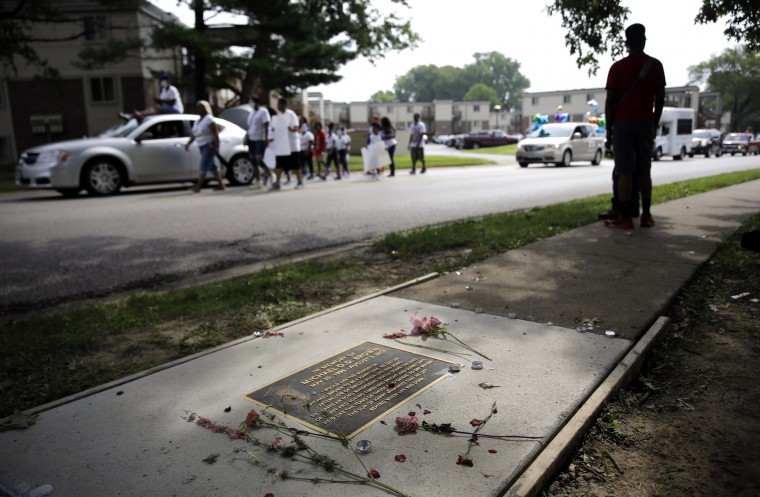 A memorial in memory of Michael Brown is seen in a sidewalk near where Brown was shot and killed as a parade in honor of Brown passes by Saturday, Aug. 8, 2015, in Ferguson, Mo. Sunday will mark one year since Brown was shot and killed by Ferguson police officer Darren Wilson. (Jeff Roberson/Associated Press)