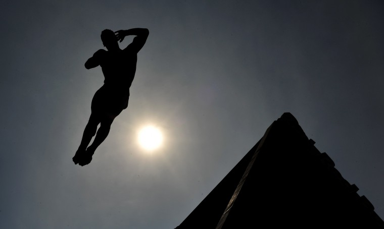"A competitor dives during the Cliff Diving World Series competition in the Southern-Bosnian city of Mostar on August 15, 2015. Competitors jump from a platform installed on Mostar's ""Old Bridge"", that crosses the Neretva river, where the height of the dive is around 28 meters, the dive takes about 3 seconds. (Elvis Barukcic/AFP-Getty Images)"