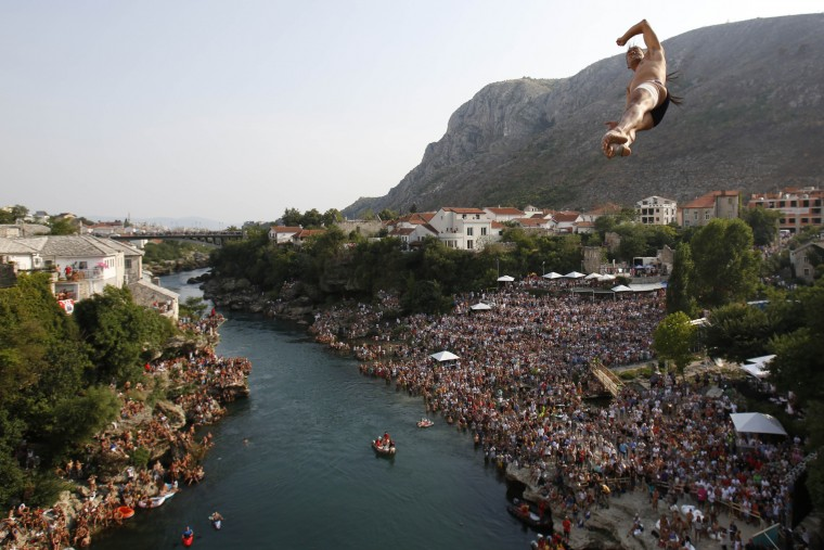 Competitors dive from the Old Mostar Bridge during the sixth stop of the Red Bull Cliff Diving World Series 2015, in Mostar, 140 kms south of Bosnian capital of Sarajevo, Saturday, Aug. 15, 2015. Fourteen of the world's best competitors took part in the competition diving from a 27 meter high bridge over the river of Neretva. (Amel Emric/Associated Press)