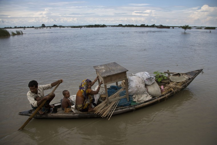 An Indian family sail through a flood-affected area in Xandohkhaitee village, about 80 kilometers (50 miles) east of Gauhati, India , Saturday, Aug. 22, 2015. State authorities say that monsoon flooding has nearly 200,000 people to leave their homes and take shelter in state-run tents this week. The area is prone to flooding during the June-to-September monsoon season. (Anupam Nath/Associated Press)