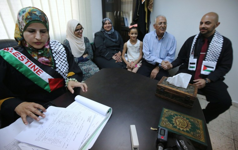 "Tahrir Hamad (L), the first Palestinian woman justice of the peace, pronounces Thaer (R) and Rawan (2-L) man and wife at the Islamic sharia law court in the West Bank city of Ramallah on August 6, 2015. Hamad became the first, and so far the only, woman appointed as a ""mazouna"" - a Muslim official authorised to carry out marriage and divorce in the Palestinian territories. Until now in the Arab world only Egypt and Abu Dhabi have appointed women to the post. (Abbas Momani/AFP-Getty Images)"