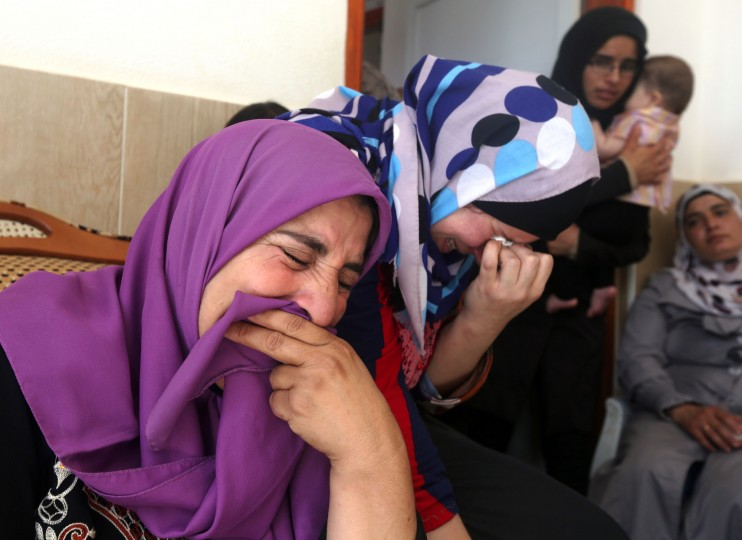 Relatives and friends of Saad Dawabsha, the father of a Palestinian toddler killed last week when their home was firebombed by Jewish extremists, mourn during his funeral in the West Bank village of Duma on August 8, 2015. Dawabsha succumbed in hospital in the southern Israeli city of Beersheba where he was being treated for third degree burns while his wife Riham and four-year-old son Ahmed are still fighting for their lives in a hospital. (Jaafar Ashtiyeh/AFP-Getty Images)