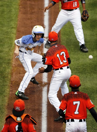 The ball gets away from Dominican Republic's Emmanuel Rodriguez (13) during a run down between third and home of Australia's Mark Natta, left, during the first inning of an International elimination baseball game at the Little League World Series tournament in South Williamsport, Pa., Saturday, Aug. 22, 2015. Natta retreated to third safely on the error. Australia won 3-0. (Gene J. Puskar/Associated Press)