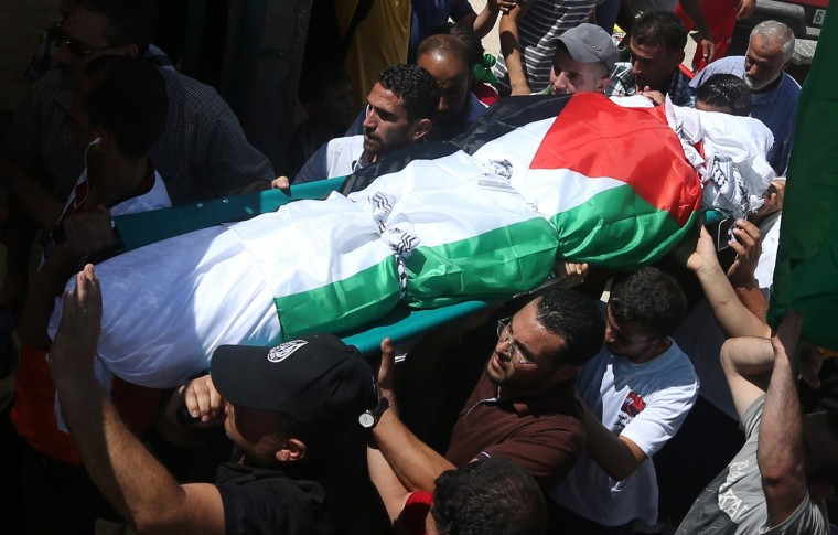 Palestinian men carry the body of Saad Dawabsha, the father of a Palestinian toddler killed last week when their home was firebombed by Jewish extremists, during his funeral in the West Bank village of Duma on August 8, 2015. Dawabsha succumbed in hospital in the southern Israeli city of Beersheba where he was being treated for third degree burns while his wife Riham and four-year-old son Ahmed are still fighting for their lives. (Jaafar Ashtiyeh/AFP-Getty Images)