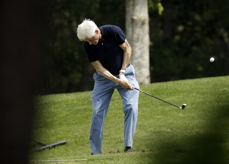 Former President Bill Clinton follows through with his swing while golfing Saturday, Aug. 15, 2015, at Farm Neck Golf Club, in Oak Bluffs, Mass., on the island of Martha's Vineyard. Clinton golfed with President Barack Obama, who is vacationing on the island with his family. (Steven Senne/Associated Press)