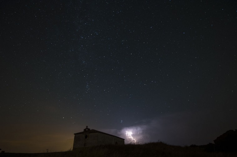 Stars and storms seen as streaks from a long camera exposure are seen behind an ancient Hermitage, in Murillo del Fruto, northern Spain, Wednesday, Aug. 12, 2015. The meteor shower is expected to peak Wednesday night into Thursday morning. (AP Photo/Alvaro Barrientos)