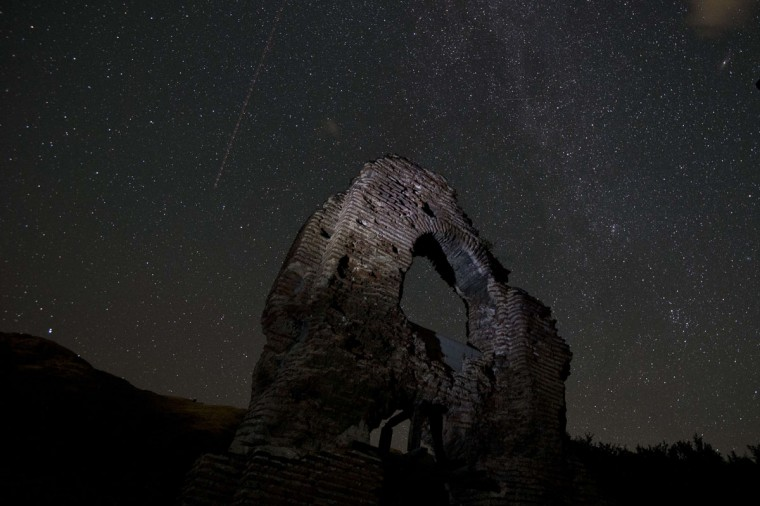 A long exposure image showing an airplane passing in the sky during the Perseids meteor shower over the remains of St. Ilia Roman, an early Christian basilica dated back to the 5th or 6th century AD near the town of Pirdop, early on August 12, 2015. The Perseid meteor shower occurs every year in August when the Earth passes through the debris and dust of the Swift-Tuttle comet. The Perseid meteor shower -- an annual display of natural fireworks -- should be particularly spectacular this year, with extra-dark skies expected to create optimal stargazing conditions, astronomers said on August 7, 2015. (NIKOLAY DOYCHINOV/AFP/Getty Images)
