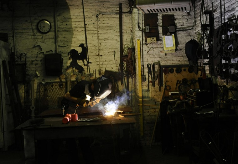 Evan Price, Reservoir Hill, a fabricator for G. Krug & Son Ironworks, works to repair an urn leg from the Washington Monument at Mount Vernon Place on Oct. 8, 2014. (Kim Hairston/The Baltimore Sun)