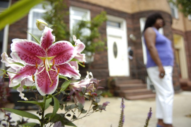"Residents of Reservoir Hill have set out to improve their community by planting trees, clearing vacant lots and gardening them, and even starting a ""farm"" to grow and produce fresh vegetables and fruits that residents have a hard time getting at the corner stores. -- Jerrie Okwesa stands outside her home on Newington Ave., on July 7, 2011. (Gabe Dinsmoor / Baltimore Sun)"