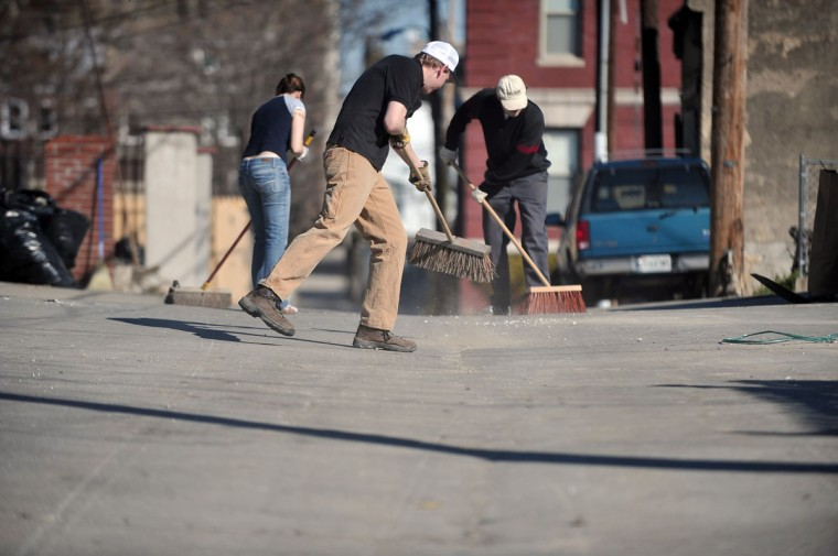 From left, Esther Mena, Jeff Marks and Thor Nelson, residents of Linden Avenue, clean the alley between their street and Eutaw Place on April 18, 2009. (Kim Hairston / Baltimore Sun)