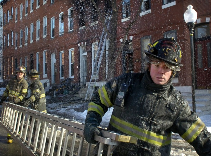 Baltimore firefighters from Truck 5 return a ladder to their truck after getting a one-alarm fire at 1809 Park Avenue under control on February 16, 2007. (Baltimore Sun photo by Amy Davis)