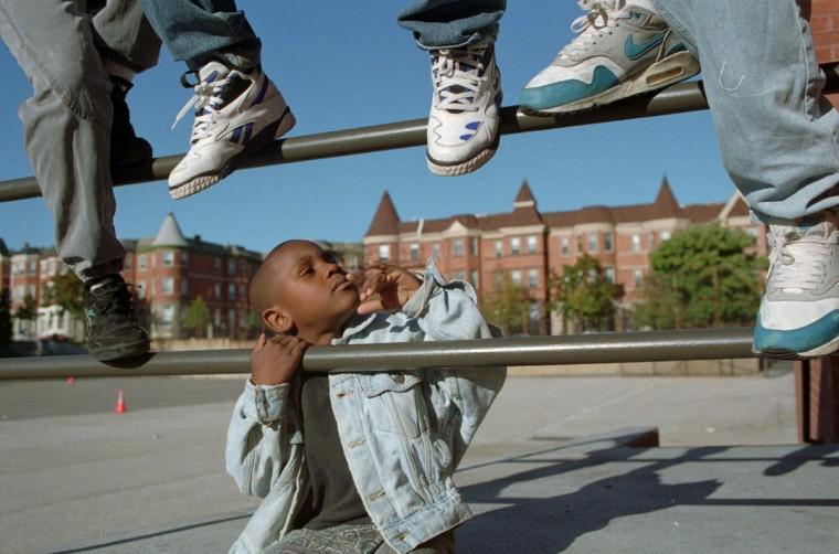 Michael Epps, 6, of Reservoir Hill, is surrounded by shoes. (Kim Hairston / Baltimore Sun / Oct. 5, 1993)