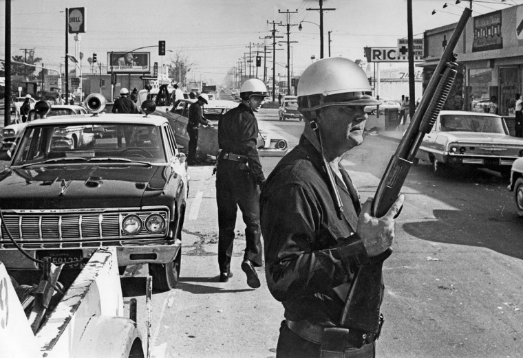 Los Angeles police officers stand guard as debris from a day of violence is cleared from the intersection of Avalon Boulevard and Imperial Highway, one of the worst trouble spots from which violence was spreading, on Aug. 13, 1965. (Ray Graham/Los Angeles Times/TNS)