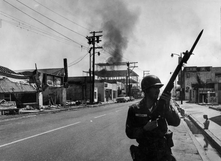 A California National Guardsman patrols 103rd Street near Compton Avenue in the Watts business district on Aug. 14, 1965. (Ray Graham/Los Angeles Times/TNS)