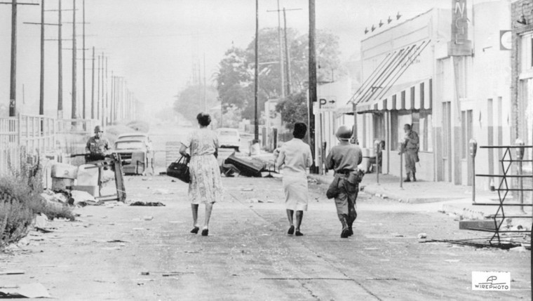 A rifle-carrying National Guardsman escorts two women through the debris-littered streets of Watts, where rifle fire from snipers continued to harass black and white people alike in Los Angeles' riot zone. The women were bound for Sunday church services on August 15, 1965. (AP Wirephoto.)
