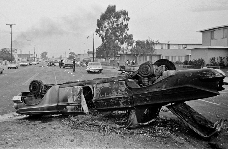 In this Aug. 13, 1965 file photo, the burned-out hulk of an overturned automobile, foreground, and other burned cars at rear block the street at Imperial Highway and Avalon Boulevard during rioting in the Watts district of Los Angeles. It began with a routine traffic stop 50 years ago this month, blossomed into a protest with the help of a rumor and escalated into the deadliest and most destructive riot Los Angeles had seen. The Watts riot broke out Aug. 11, 1965 and raged for most of a week. When the smoke cleared, 34 people were dead, more than a 1,000 were injured and some 600 buildings were damaged. (AP Photo/Harold Filan, File)