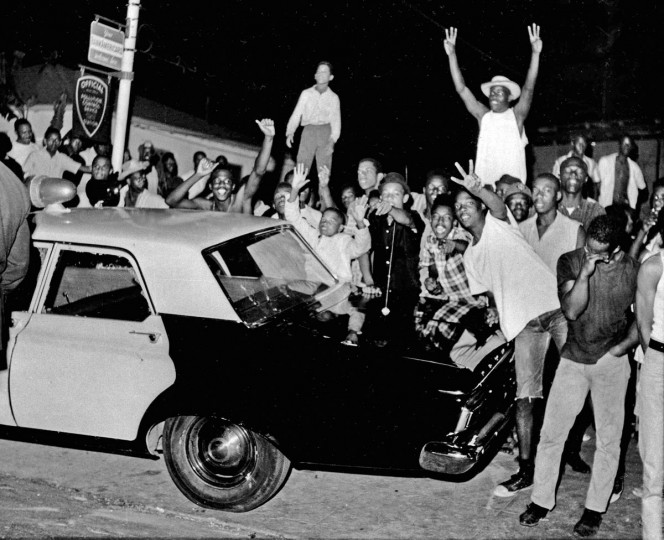 In this Aug. 12, 1965 file photo, demonstrators push against a police car after rioting erupted in the Watts district of Los Angeles. It began with a routine traffic stop 50 years ago this month, blossomed into a protest with the help of a rumor and escalated into the deadliest and most destructive riot Los Angeles had seen. The Watts riot broke out Aug. 11, 1965 and raged for most of a week. When the smoke cleared, 34 people were dead, more than a 1,000 were injured and some 600 buildings were damaged. (AP Photo, File)