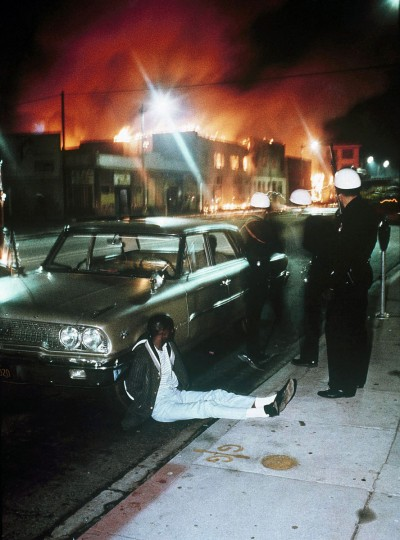 In this August, 1965 file photo, police detain a man as buildings burn during rioting that swept the Watts district of Los Angeles. It began with a routine traffic stop 50 years ago this month, blossomed into a protest with the help of a rumor and escalated into the deadliest and most destructive riot Los Angeles had seen. The Watts riot broke out Aug. 11, 1965 and raged for most of a week. When the smoke cleared, 34 people were dead, more than a 1,000 were injured and some 600 buildings were damaged. (AP Photo, File)
