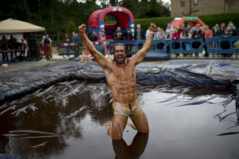 Joel Hicks celebrates winning the men's title in the 8th annual World Gravy Wrestling Championships at the Rose n Bowl Pub in Bacup, north west England on August 31, 2015. (OLI SCARFF/AFP/Getty Images)