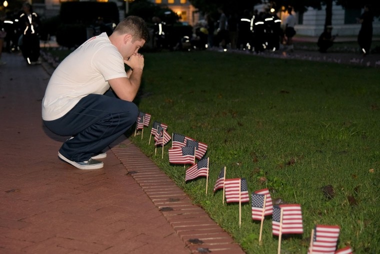 After placing his last flag, Midshipman 2nd Class Reilly Klein, of Richmond, VA., says a prayer for his uncle Daniel Suhr, a member of the FDNY killed on 9/11. Midshipmen at the U.S. Naval Academy placed 2977 flags along Stribling Walk, one for each person killed in the September 11th Attacks on the World Trade Center and Pentagon. The event was sponsored by the Midshipmen Action Group.