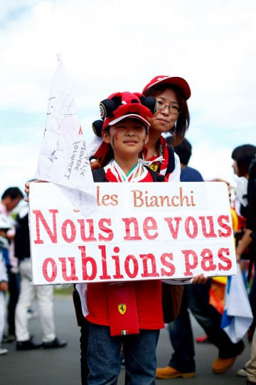 Fans pose with a tribute to the late formula one driver Jules Bianchi before final practice for the Formula One Grand Prix of Japan at Suzuka Circuit on September 26, 2015 in Suzuka. (Clive Rose/Getty Images)