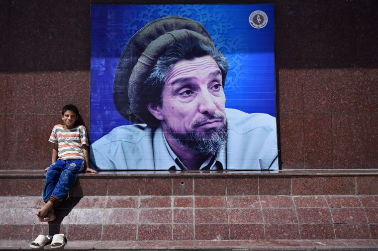 "An Afghan boy sits next to poster bearing the image of the late resistance leader Ahmad Shah Massoud as his fourteenth death anniversary is marked in Kabul on September 9, 2015. Massoud, nicknamed the ""Lion of the Panjshir"" for his armed struggle against the Taliban that ruled Afghanistan at the time, died September 9, 2001 when two Tunisians posing as journalists with fake Belgian passports detonated a bomb hidden in the camera as they pretended to interview him. His death, just two days before the September 11 attacks in New York and Washington, has been linked to Osama bin Laden's al-Qaeda network by US officials. (AFP Photo/Wakil Kohsar)"