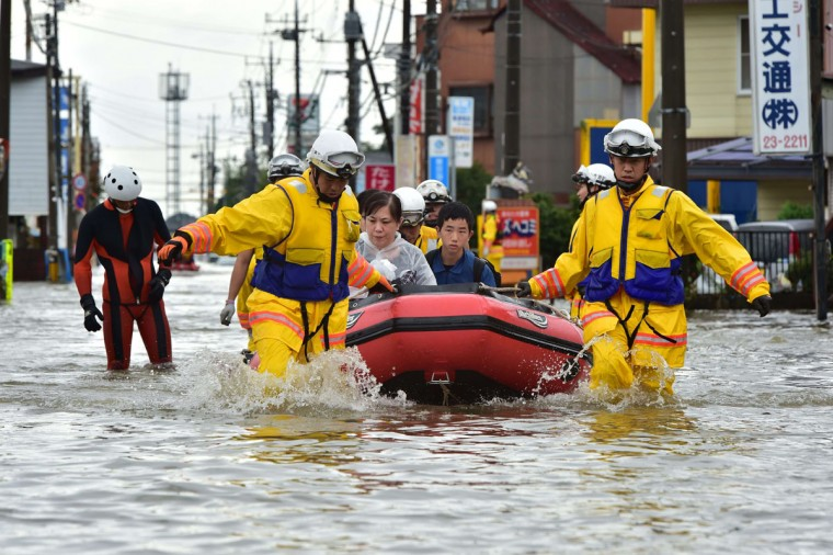 Rescue workers transport evacuees in a rubber boat through floodwaters at Oyama in Tochigi prefecture, north of Tokyo on September 10, 2015. Authorities in central Japan ordered tens of thousands to flee their homes after torrential rains flooded rivers and triggered landslides, with one person missing after a mudslide buried houses. The Japan Meteorological Agency issued special downpour warnings for Tochigi and Ibaraki prefectures, north of Tokyo, urging vigilance against mudslides and flooding. (AFP Photo/Yoshikazu Tsuno)