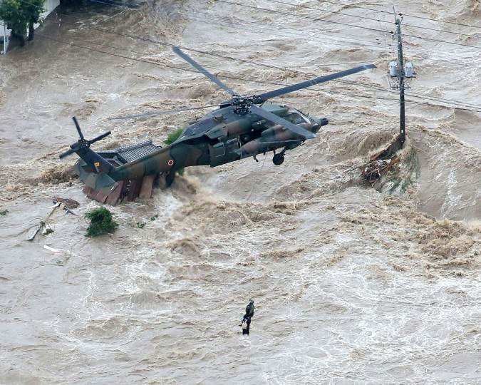 A local resident is rescued by a helicopter of the Gound Self Defense Force in a flooded area in Joso, Ibaraki Prefecture, on September 10, 2015. The Japanese city 50 km north east of Tokyo was flooded when Kinugawa river burst its banks, destroying homes and cars as desperate residents waited for help, and as thousands of people were ordered to evacuate. (AFP Photo/P /jiji )