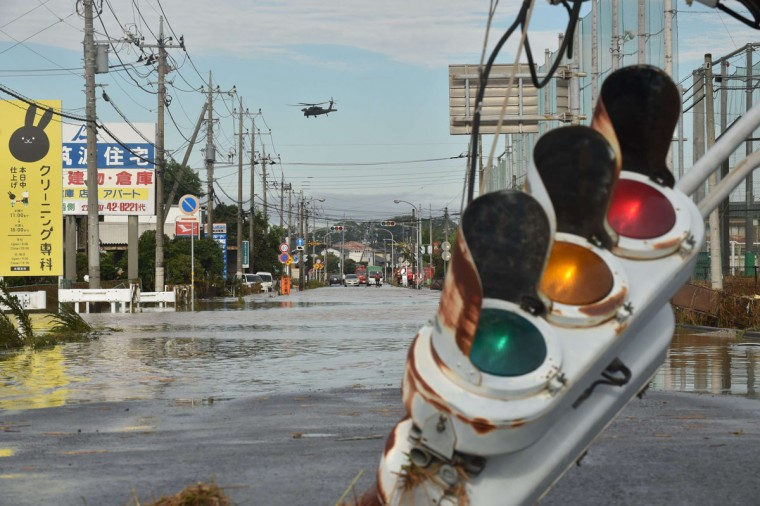 A military helicopter flies over a flooded street during a rescue mission in the city of Joso in Ibaraki prefecture on September 11, 2015. Thousands of rescuers arrived in a deluged city north of Tokyo on September 11 to help evacuate hundreds of trapped residents and search for 12 people missing after torrential rains triggered massive flooding. (AFP Photo/Kazuhiro Nogi)