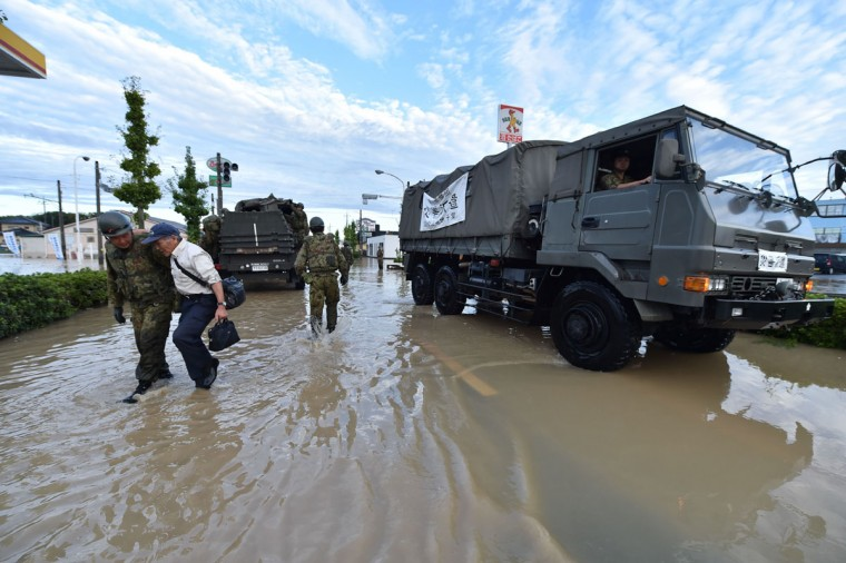 A man is helped by a military rescue worker (L) on a flooded street in the city of Joso in Ibaraki prefecture on September 11, 2015. Thousands of rescuers arrived in a deluged city north of Tokyo on September 11 to help evacuate hundreds of trapped residents and search for 12 people missing after torrential rains triggered massive flooding. (AFP Photo/Kazuhiro Nogi)