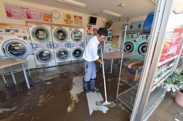 A man attempts to clear muddy floodwaters from a launderette in the city of Joso in Ibaraki prefecture on September 11, 2015. Thousands of rescuers arrived in a deluged city north of Tokyo on September 11 to help evacuate hundreds of trapped residents and search for 12 people missing after torrential rains triggered massive flooding. (AFP Photo/Kazuhiro Nogi)