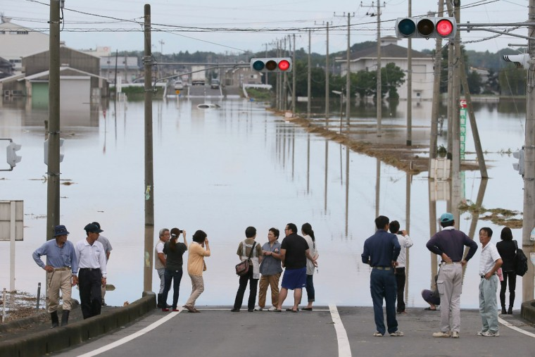 People stand near a flooded area in the city of Joso in Ibaraki prefecture on September 11, 2015. Thousands of rescuers arrived in a deluged city north of Tokyo on September 11 to help evacuate hundreds of trapped residents and search for 12 people missing after torrential rains triggered massive flooding. (AFP Photo/Jiji japan outjiji press)