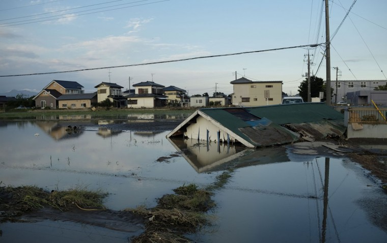 This picture shows a collapsed house in a flooded paddy field in Joso city, Ibaraki prefecture on September 11, 2015. Thousands of rescuers arrived in a deluged city north of Tokyo on September 11 to help evacuate hundreds of trapped residents and search for 12 people missing after torrential rains triggered massive flooding. (AFP Photo/Kazuhiro Nogi)