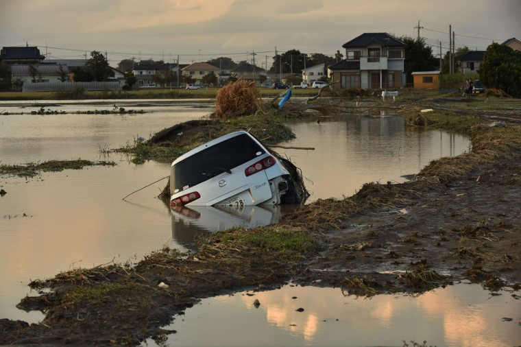 This picture shows a vehicle submerged in a flooded paddy field in Joso city, Ibaraki prefecture on September 11, 2015. Thousands of rescuers arrived in a deluged city north of Tokyo on September 11 to help evacuate hundreds of trapped residents and search for 12 people missing after torrential rains triggered massive flooding. (AFP Photo/Kazuhiro Nogi)