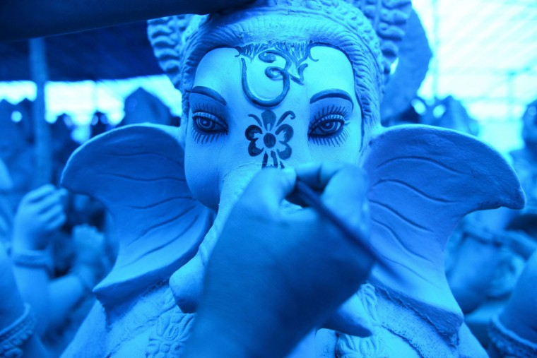 An Indian artist works on eco-friendly figures of Hindu God Lord Ganesh made with mud, jute and bamboo at a blue tarp-covered workshop on the outskirts of Hyderabad on September 15, 2015. The statues of eco-friendly clay Ganesh idols made with mud, jute and bamboo will reduce pollution during the Ganesh immersion. The popular eleven-day long Hindu religious festival, Ganesh Chaturthi will be celebrated from September 17-27 this year. (Noah Seelam/AFP/Getty Images)