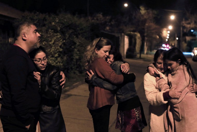 People remain in the street during a strong quake in Santiago on September 16, 2015. A strong 7.2-magnitude earthquake struck the center of Chile on Wednesday, local seismologists said, triggering a tsunami alert, sparking panic and shaking buildings. (AFP Photo/P )