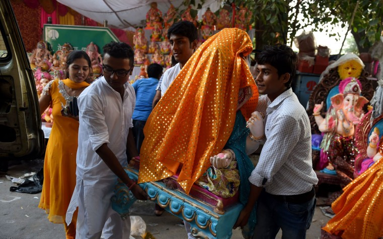 Indian devotees carry an idol of elephant headed Hindu God Lord Ganesha after purchasing it from a roadside market in New Delhi on September 17, 2015, at the start of the Ganesh Chaturthi Festival. Hindu devotees bring home idols of Lord Ganesh in order to invoke his blessings for wisdom and prosperity during the 11-day long festival, which culminates with the immersion of the idols in water on September 27. (Money Sharma/AFP/Getty Images)