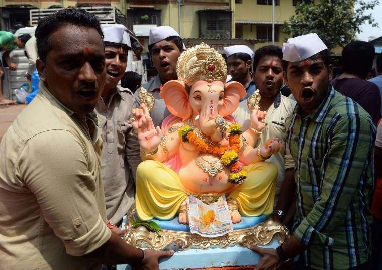 Indian Hindu devotees carry an idol of the elephant-headed Hindu god Lord Ganesha for Ganesh Chaturthi in Mumbai on September 17, 2015. The Ganesh Chaturthi festival, a popular 11-day religious festival which is annually celebrated across India, runs this year from September 17-27, and culminates with the immersion of the idols in the Arabian Sea and local water bodies. (Indranil Mukherjee/AFP/Getty Images)