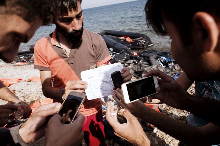 Refugees use mobile phones to take pictures of a map upon their arrival on Eftalou beach, west of the port of Mytilene, on the Greek island of Lesbos after crossing the Aegean sea from Turkey on September 21, 2015. Europe's migrant crisis took centre-stage at the UN human rights council, as European states said the need to end the conflict in Syria was at an all-time high. (AFP Photo/Iakovos Hatzistavrou)