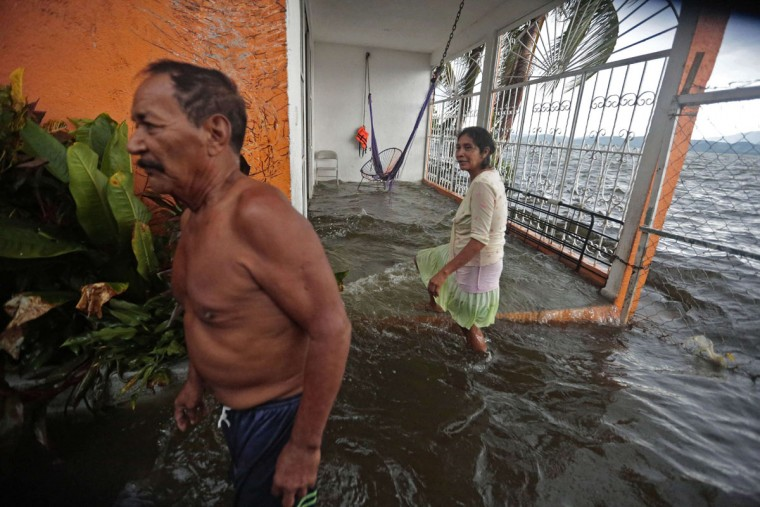 A couple remains at a flooded house due to the overflowing of the Coyuca lagoon in Acapulco, Guerrero State, Mexico, on September 29, 2015, during the passage of tropical storm Marty. Marty, which had reached hurricane force at its peak, was downgraded to a tropical storm Tuesday as it churned in the Pacific Ocean off the coast of Mexican resort town Acapulco. (AFP Photo/Pedro Pardo)