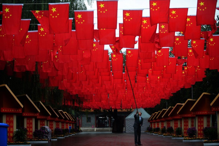 This photo taken on September 29, 2015 shows a worker adjusting Chinese national flags following rain at Badachu in Beijing ahead of Chinese National Day. (AFP Photo)