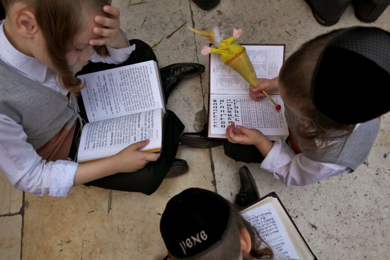 Ultra-Orthodox Jewish children sit on the floor and pray as they attend the annual Cohanim prayer (priest's blessing) during the Sukkot, or the feast of the Tabernacles, holiday at the Western Wall in the old city of Jerusalem on September 30, 2015. Tens of thousands of Jews make the week-long pilgrimage to Jerusalem during Sukkot, which commemorates the desert wanderings of the Israelites after their exodus from Egypt. (AFP Photo/Gil Cohen magen)