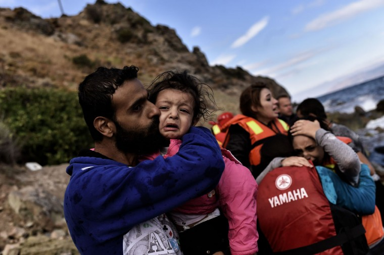A man kisses his child as refugees and migrants arrive to the Greek island of Lesbos after crossing the Aegean sea from Turkey on September 30, 2015. Europe's migrant crisis was set to be in focus at the UN with Secretary General Ban Ki-moon seeking to muster a global response to the exodus of vast numbers of people from Syria and elsewhere. (AFP Photo/Aris Messinis)