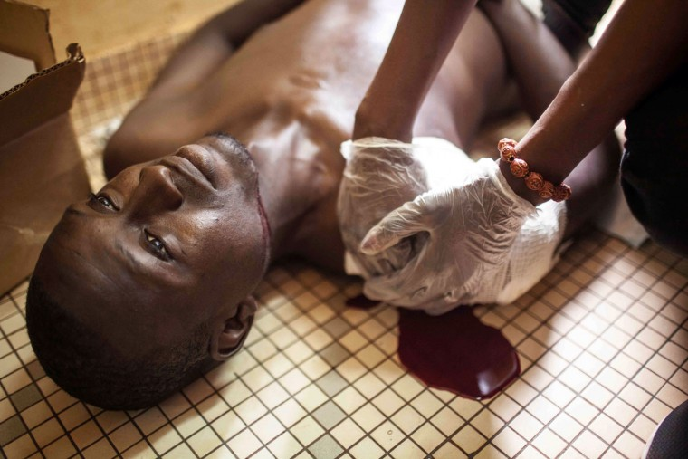 A protester who was shot during clashes is treated in a hospital in Ouagadougou, Burkina Faso, Thursday, Sept. 17, 2015. The protester later died. While gunfire rang out in the streets, Burkina Faso's military took to the airwaves Thursday to declare it now controls the West African country, confirming that a coup had taken place just weeks before elections. (AP Photo/Theo Renaut)