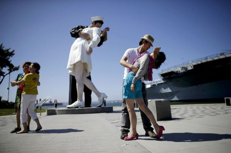 "Jie Quan, second from right, of China, dips Juan Wang, also of China, as they pose for family members in front of the sculpture ""Unconditional Surrender,"" Friday, Sept. 18, 2015, in San Diego. The sculpture by Seward Johnson is inspired by Alfred Eisenstaedt's iconic photo of a sailor kissing a nurse in Times Square on V-J Day. (AP Photo/Gregory Bull)"