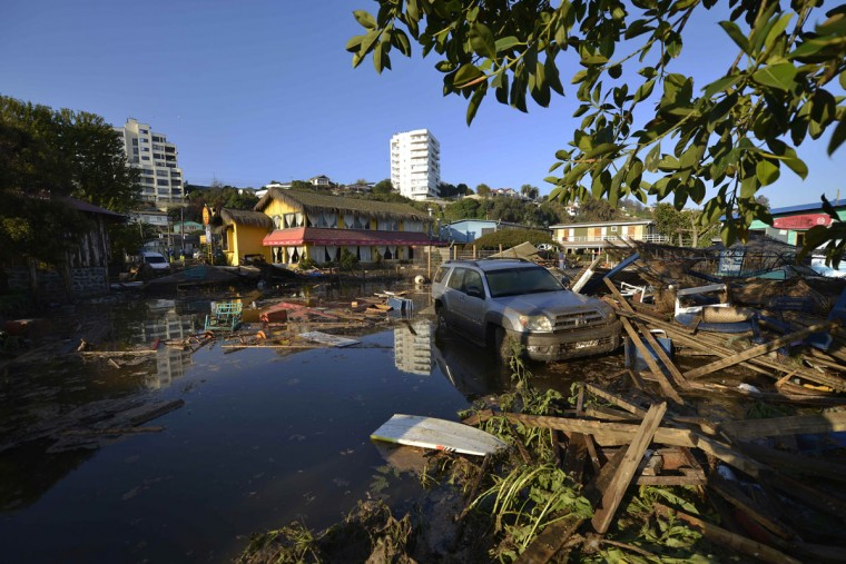 A car is surrounded by debris in a flooded street after an earthquake-triggered tsunami hit Concon, Chile, Thursday, Sept. 17, 2015. Several coastal towns were flooded from small tsunami waves set off by late Wednesday's magnitude-8.3 earthquake, which shook the Earth so strongly that rumbles were felt across South America. (AP Photo/Matias Delacroix)