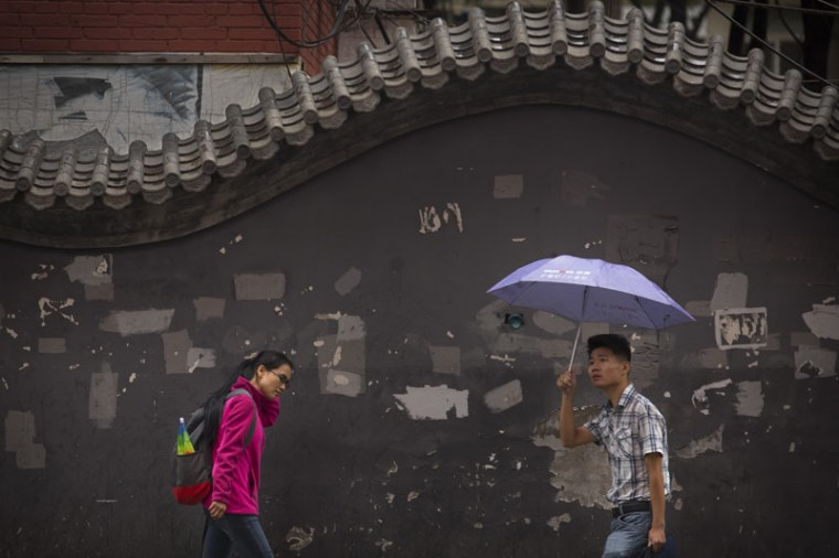 People walk along the street during a rain shower in Beijing, Tuesday, Sept. 29, 2015. China marked the Mid-Autumn Fesival on Sunday, traditionally a harbinger of cooler temperatures and more wintry conditions. (AP Photo/Mark Schiefelbein)