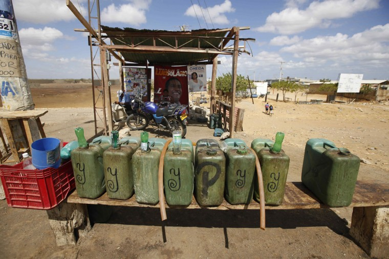 "Containers of gas sit at Victor Gonzalez's make-shift service station in Uribia, Colombia, Thursday, Sept. 10, 2015, near the border with Venezuela. Gonzalez is one of many ""pimpineros,"" salespeople who buy gas from middlemen who purchase it cheaply in Venezuela, and sell it to commuters in Colombia at closer to retail price. Gonzalez says he used to charge clients about $5 dollars per gallon before Venezuelan President Nicolas Maduro closed the border. Now he pumps it out to clients willing to pay double. (AP Photo/Fernando Vergara)"