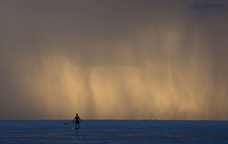 Pablo Dona, of Miami pauses while paddleboarding as sheets of rain fall in front of him, Tuesday, Sept. 22, 2015, off the shores of Bal Harbour, Fla. (AP Photo/Wilfredo Lee)